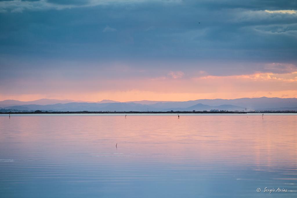 Una vez se pone el sol aparecen tonos rosas, junto a los azules de las nubes, creando degradados tonales que se reflejan en el agua.